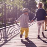 This image symbolizes young children walking on bridge holding hands whose parents went through custody mediation.