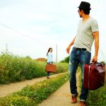 Divorcing couple walking away from each other with suitcases