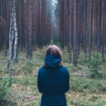 Woman looking into the woods feeling sad and frightened about her divorce